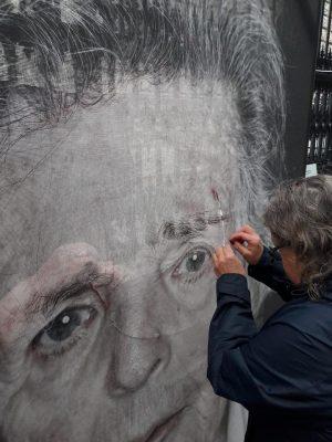 Das ist wirklich beendruckend. Menschen - jung und alt - kommen, um die aufgeschlitzten Portraits wieder zusammenzunähen....