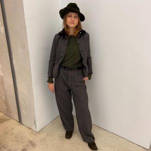 Wearing women's dorset and high blazer, trousers with belt, knit grandpa sweater, oxford shoes and haymaker hat...