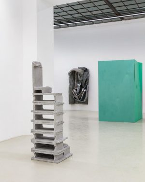'Free-standing, silvery building blocks pile up to form the narrow, permeable sculpture translation. These are aluminium casts...